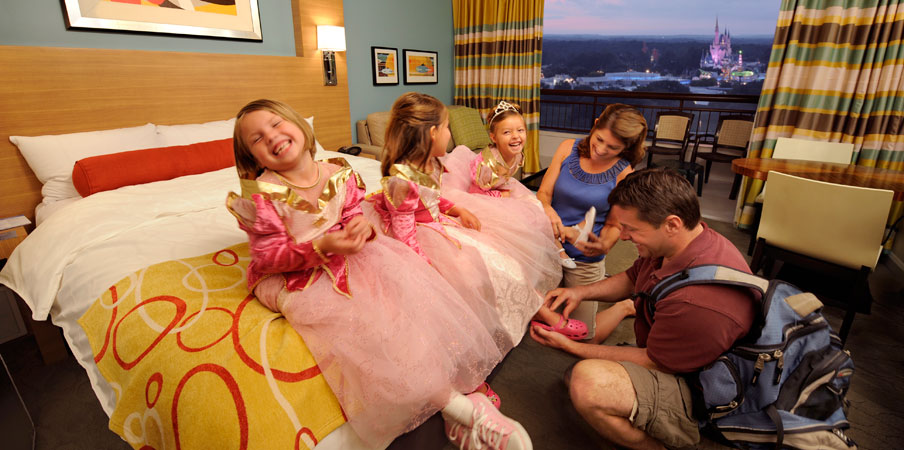Three girls dressed as princesses sitting on a bed at Bay Lake Tower at Disney's Contemporary Resort